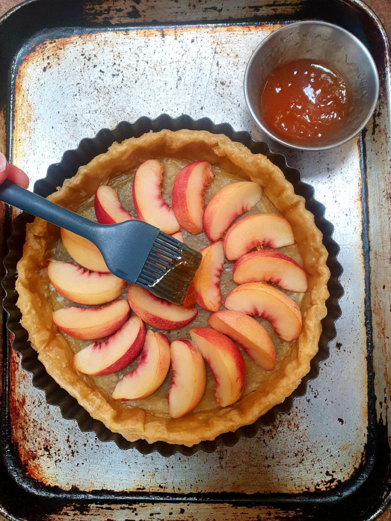 Brushing apricot jam onto nectarines in tart