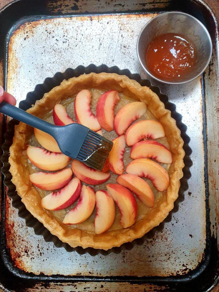 Brushing apricot jam onto nectarines in tart