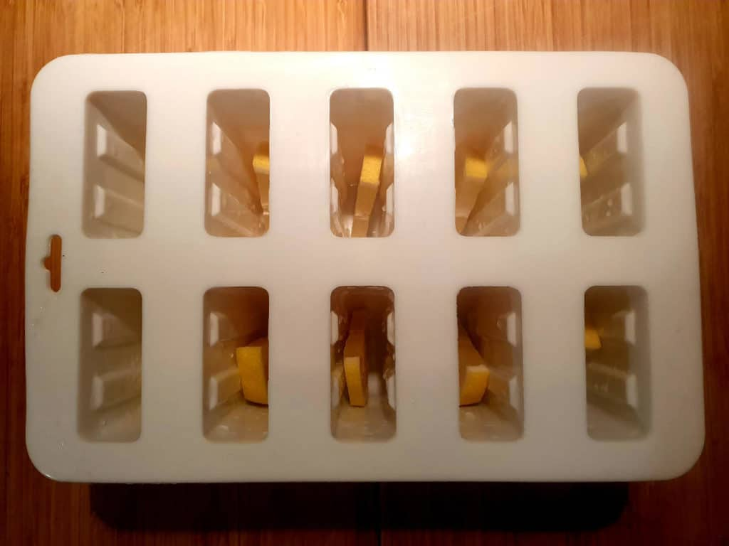 Adding lemon slices to popsicle moulds