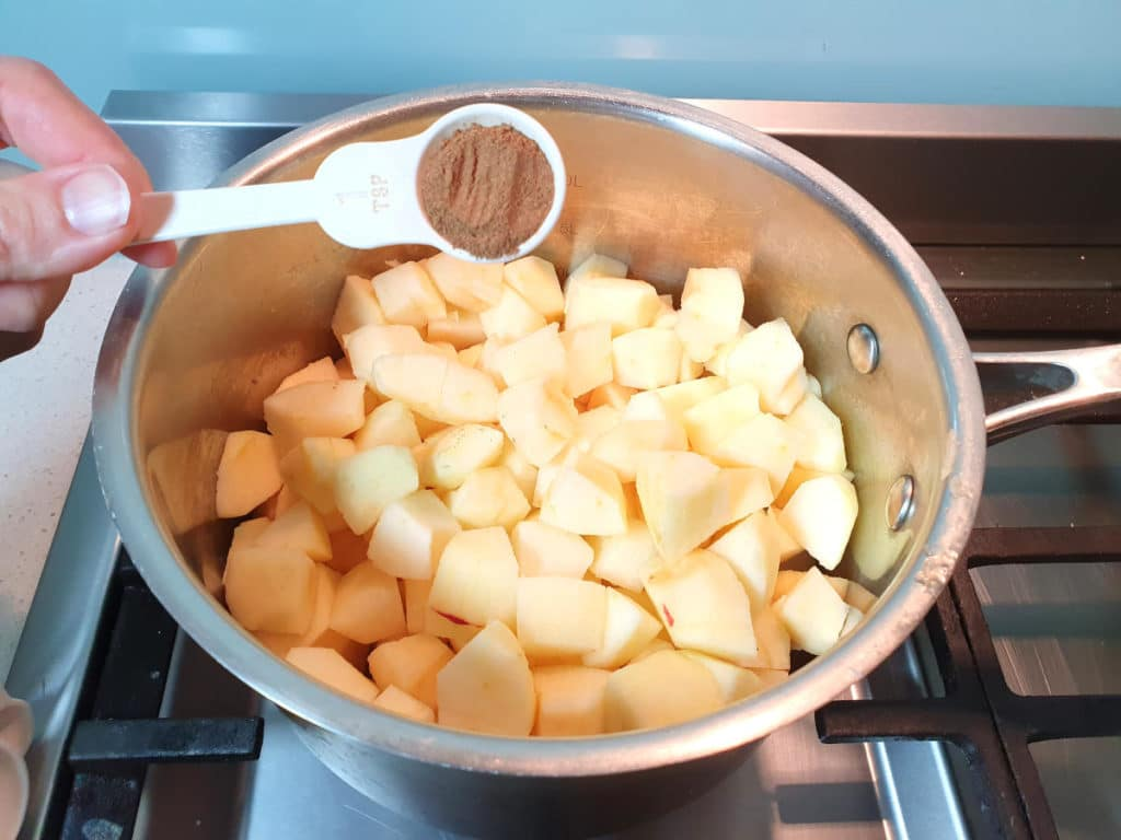 Adding cinnamon to chopped apples