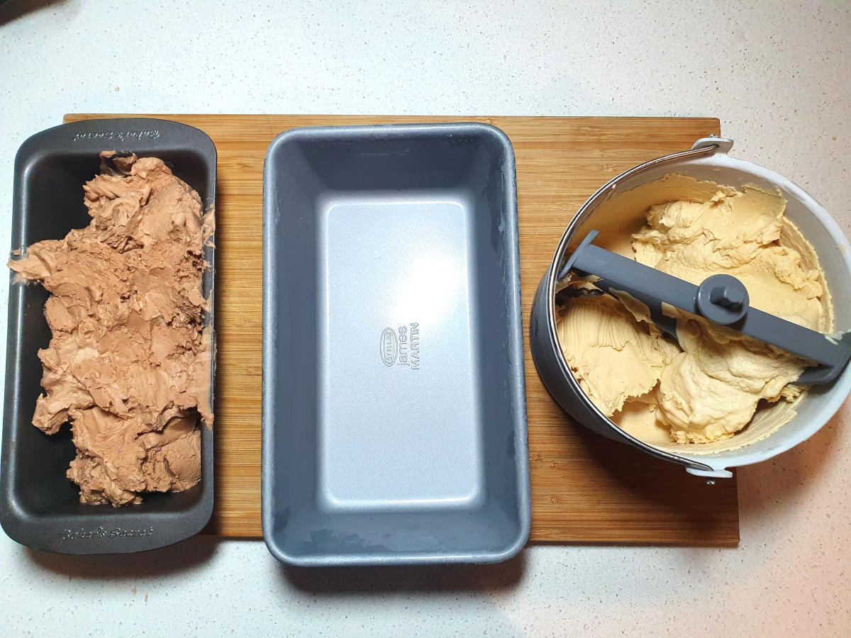 top down view of Nutella ice cream in loaf pan, empty loaf pan and peanut butter ice cream in churning bucket, on a chopping boar, on a bench.