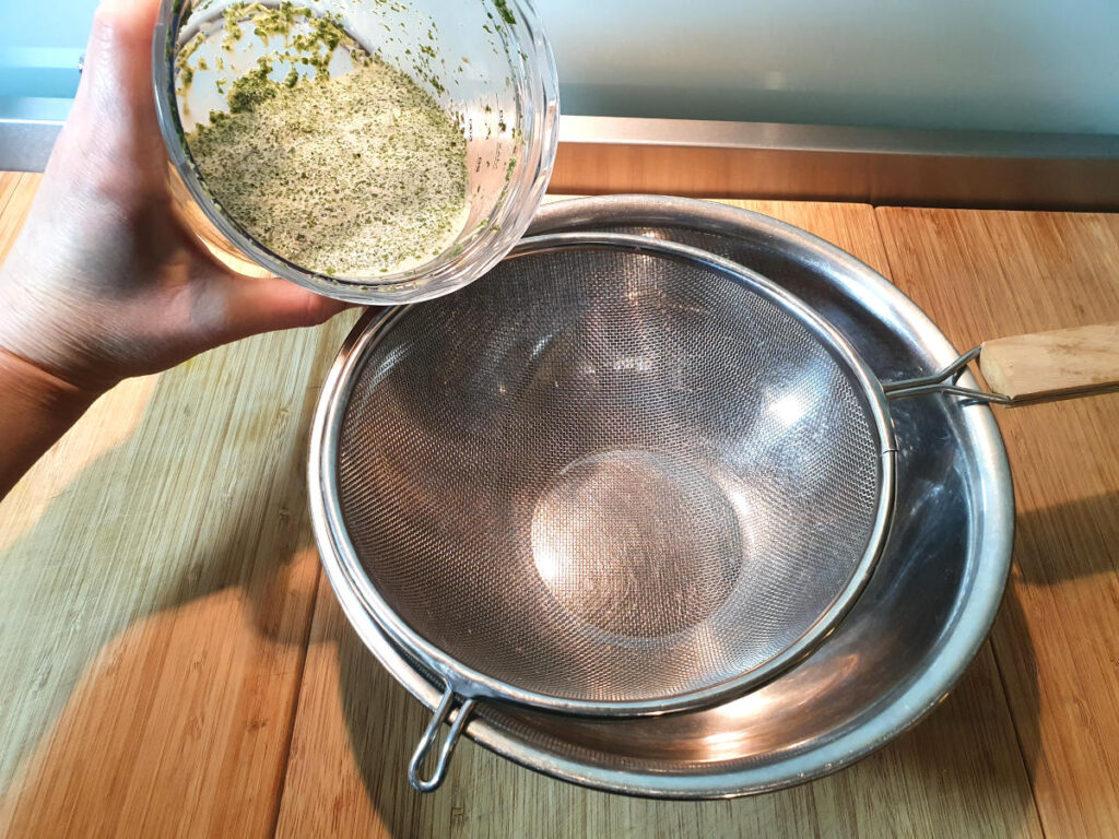 Tipping mint infused milk into strainer