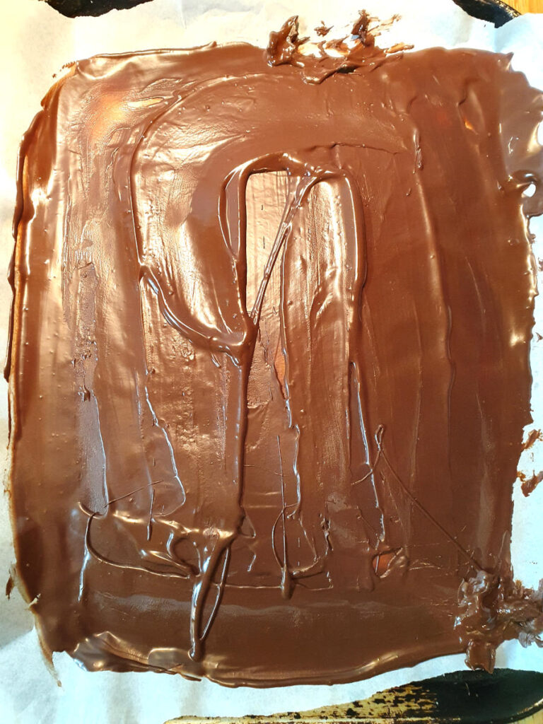 melted-chocolate spread out on grease proof paper