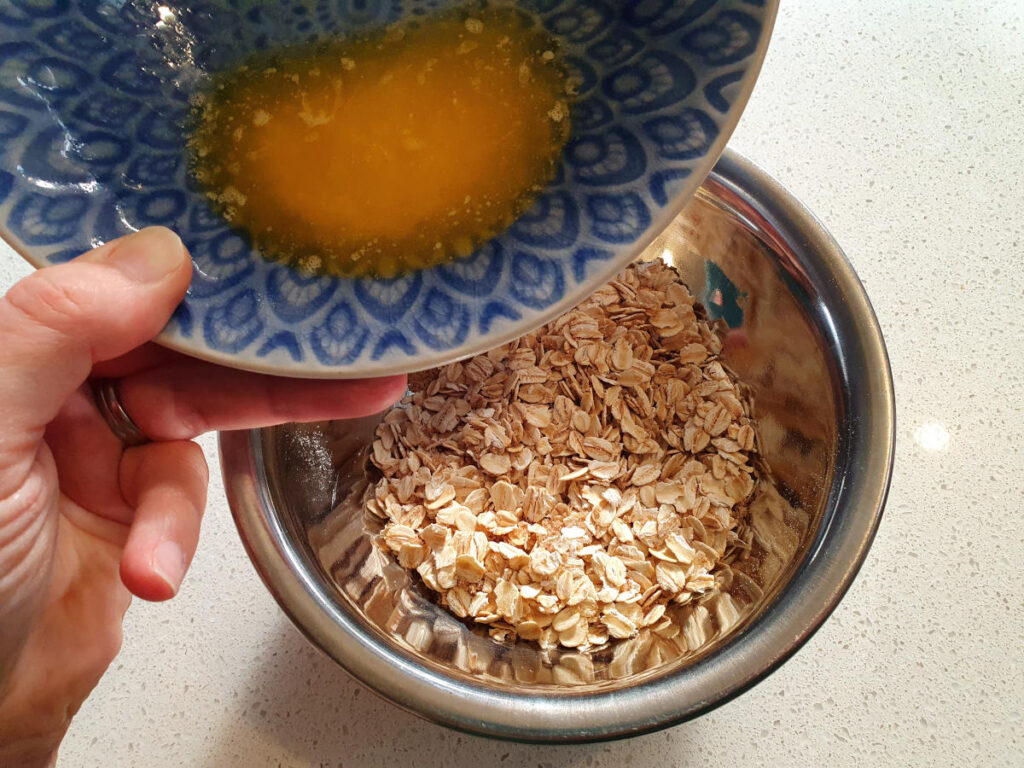 adding melted spread to oat topping
