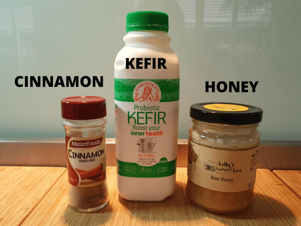 Popsicle ingredients, jar of ground cinnamon, bottle of kefir and jar of honey on a brown board with a blue background