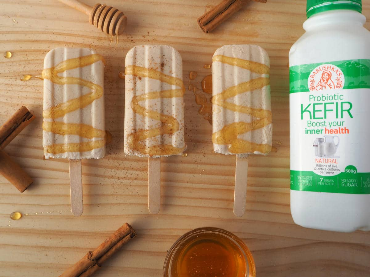 Single cinnamon, honey and kefir popsicle with honey drizzle and sprinkle of cinnamon, cinnamon stick, honey stick, honey bowl and milk kefir bottle on chopping board