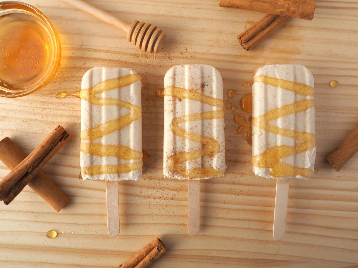 Row of three cinnamon, honey and kefir popsicles with honey drizzle and sprinkle of cinnamon, cinnamon stick, honey stick and honey bowl, on chopping board
