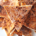 close up of pile of cinnamon sugar pita chips on a while plate.