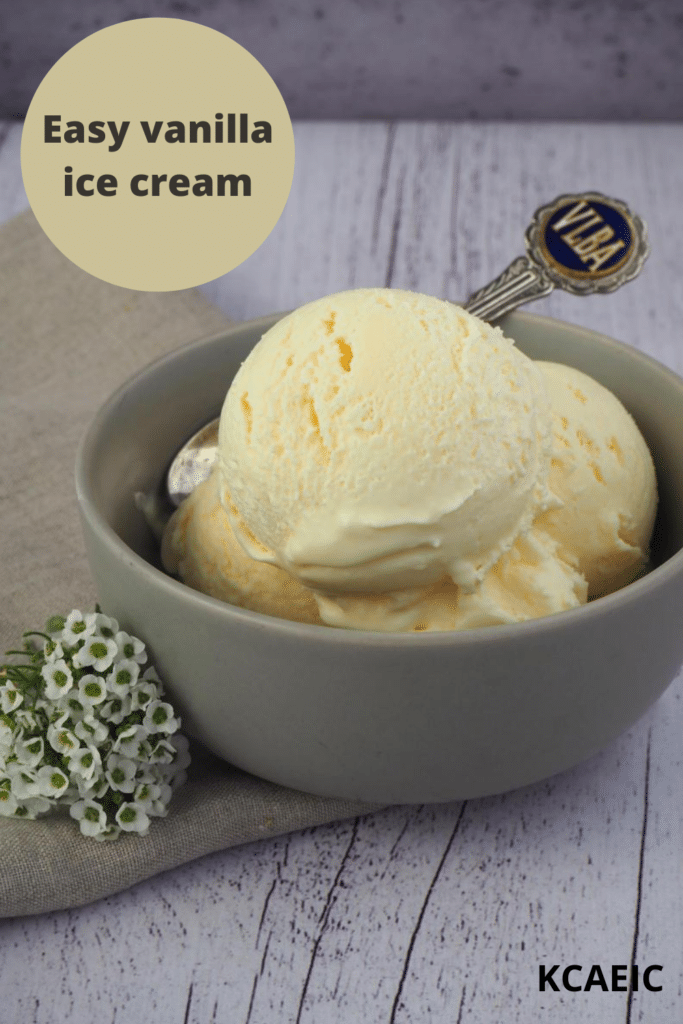 Scoops of vanilla ice ice cream in a grey bowl, with a vintage teaspoon, on a beige teatowl and a white wooded flood backgroud, with some small white flowers on the side, with text overlay, Easy vanilla ice cream and KCAEIC.