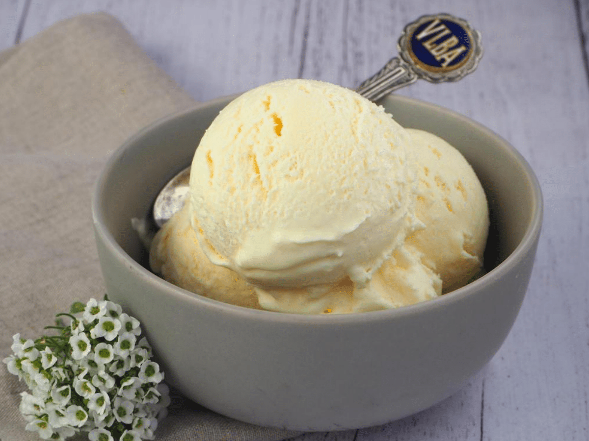 Scoops of vanilla ice ice cream in a grey bowl, with a vintage teaspoon, on a beige teatowl and a white wooded flood backgroud, with some small white flowers on the side.