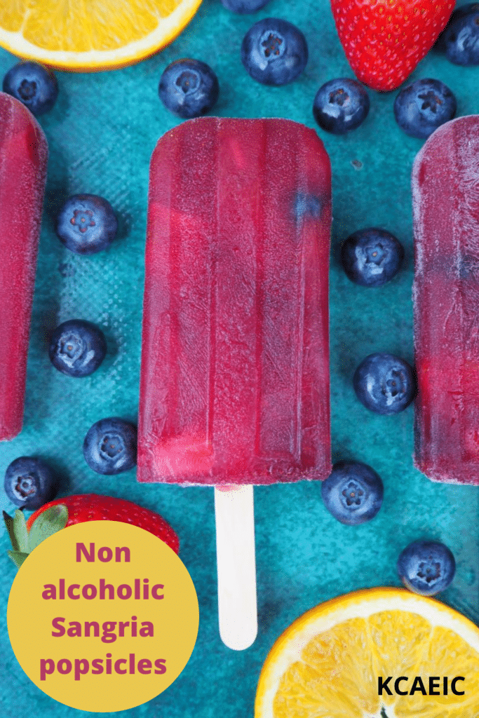 Close up of row of three non alcoholic sangria popsicle, on a green background, surrounded by strawberries, blueberries and orange slices, with text overlay, Non alcoholic sangria popsicles, KCAEIC