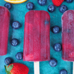 Close up of row of three non alcoholic sangria popsicle, on a green background, surrounded by strawberries, blueberries and orange slices