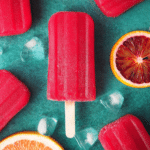 Ruby grapefruit and blood orange popsicle close up with orange and grapefruit slices and ice cubes on green background