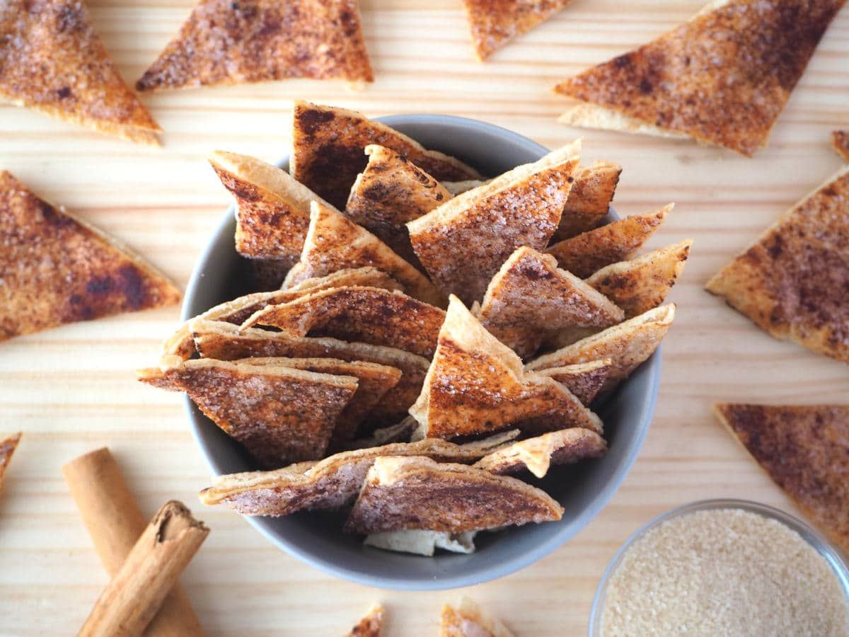 top down view of cinnamon sugar pita chips in bowl with pits chips around the sides, stacked cinnamon quills and a small glass bowl of sugar.