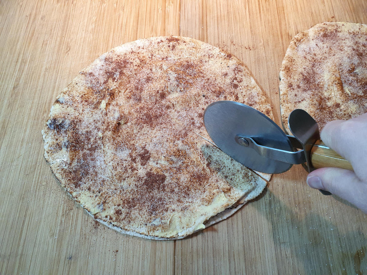cutting up pitta bread on a chopping board with a pizza cutter.
