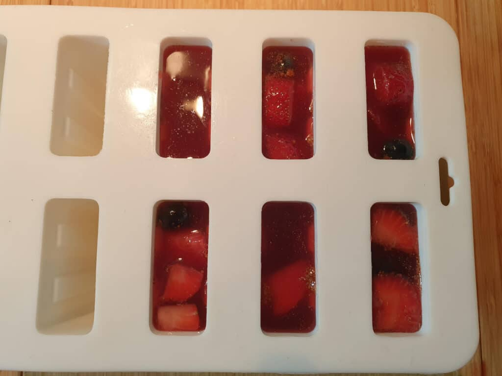 popsicle moulds filled with fruit and sangria popsicle mix