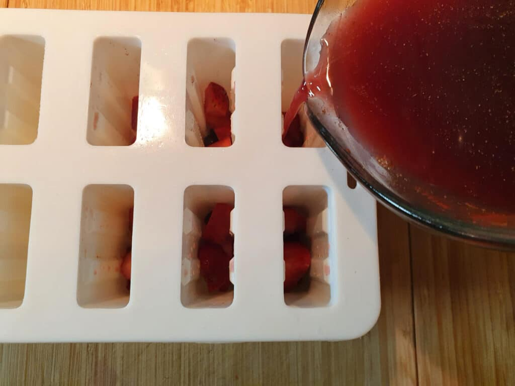 adding sangria popsicle mix to popsicle moulds