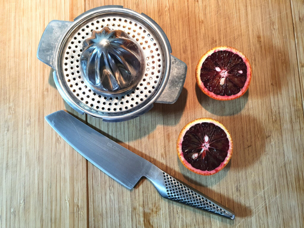 blood oranges on board with knife and juicer ready to juice