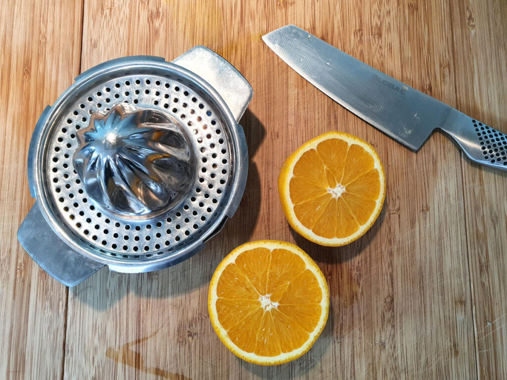 one orange cut in half on a chopping board with a knife and a juicer ready to be juiced