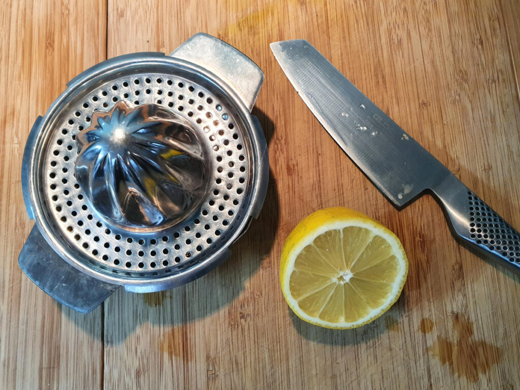one lemon orange cut in half on a chopping board with a knife and a juicer ready to be juiced