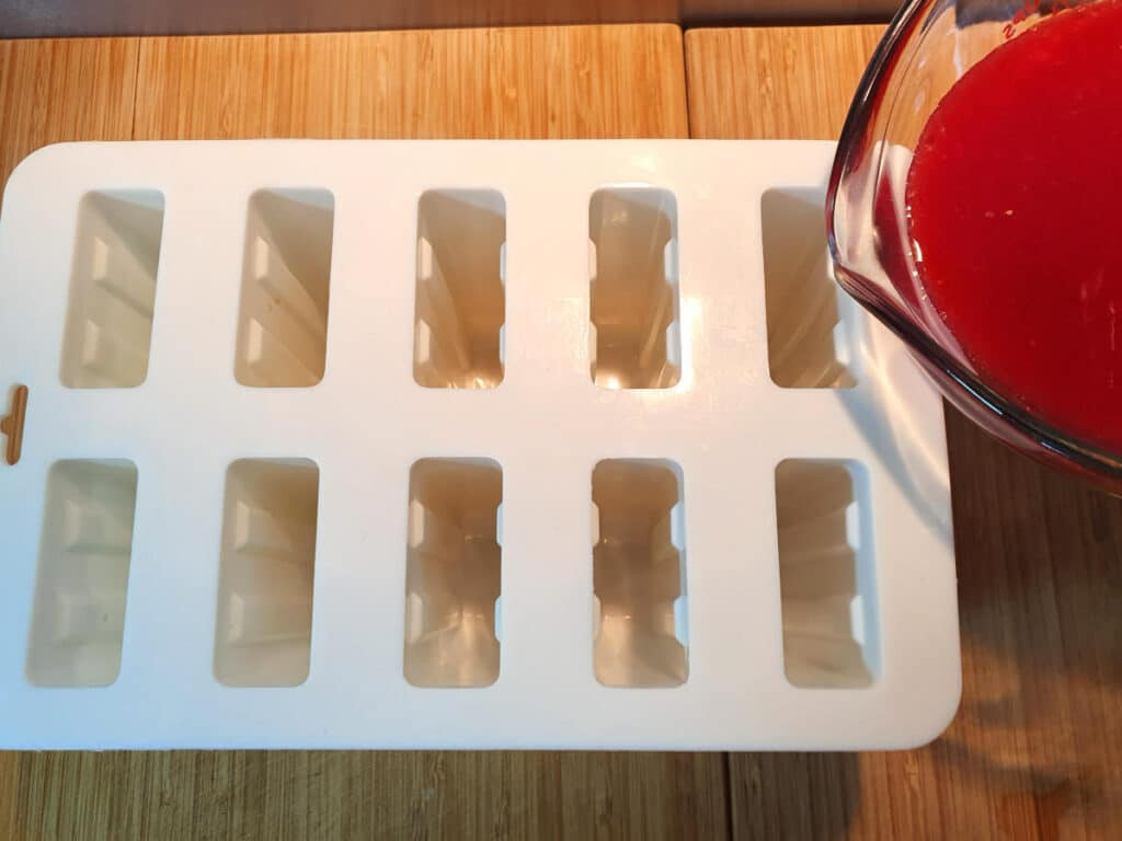 pouring popsicle mix into popsicle moulds