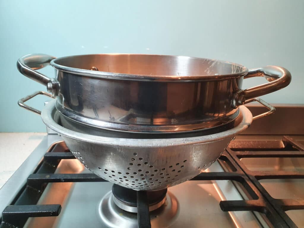 resting double boiler top in colendar on stove top