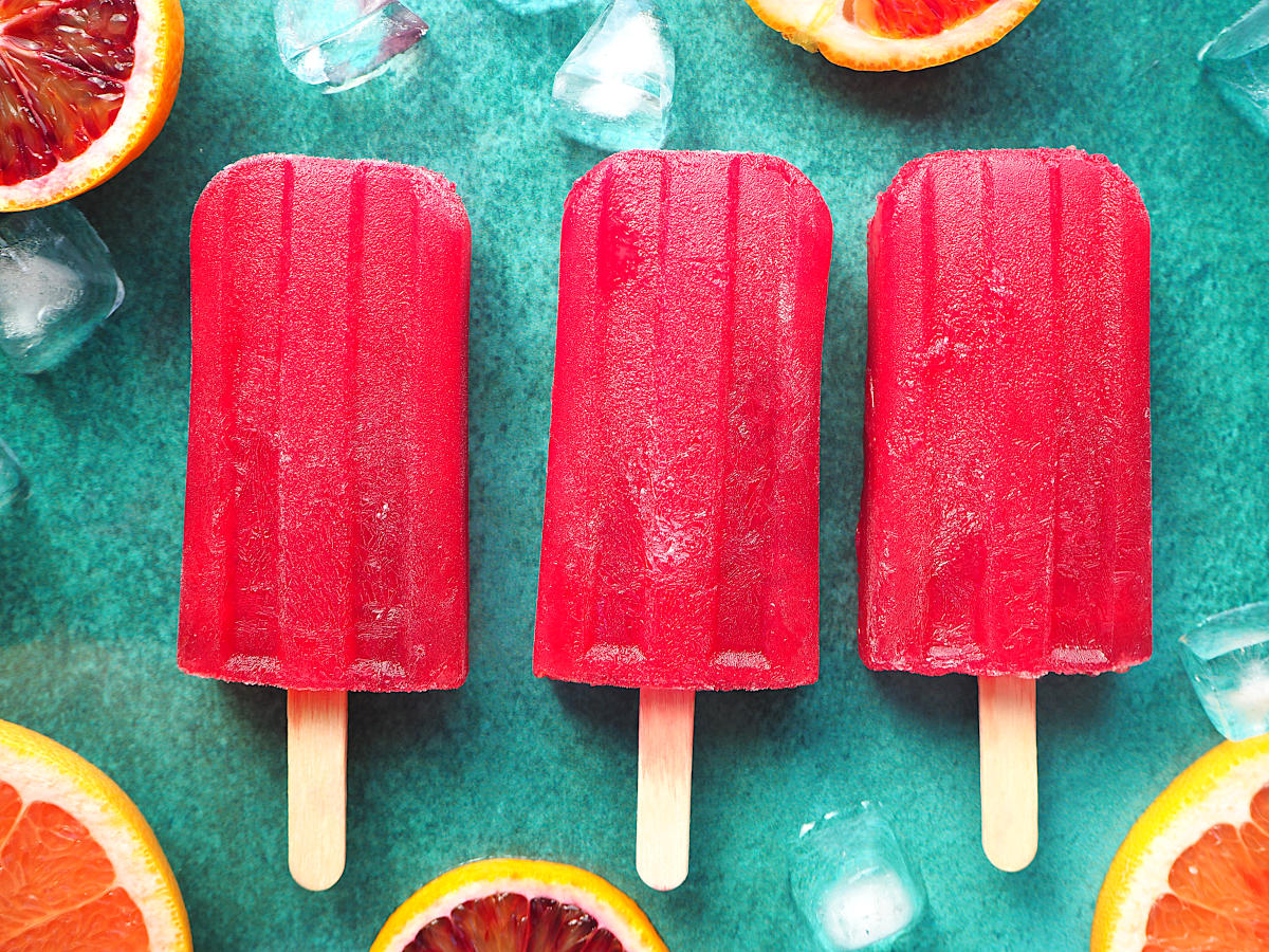 Row of three ruby grapefruit and blood orange popsicle close up with orange and grapefruit slices and ice cubes on green background