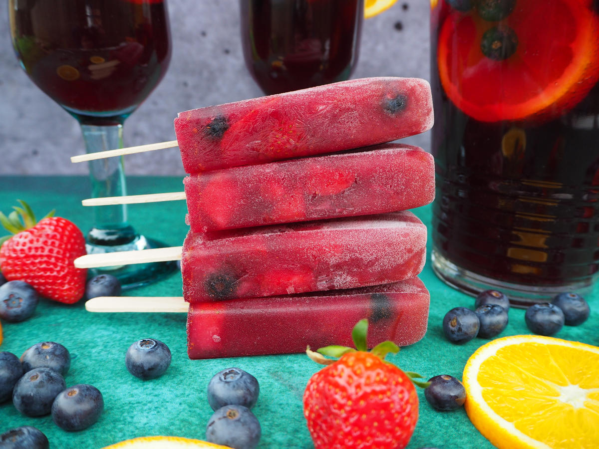 Close up of stack of four non alcoholic sangria popsicles side one, in front of a jug of sangria and two glasses of sangria, on a green background, with strawberries, blueberries and orange slices in the forground