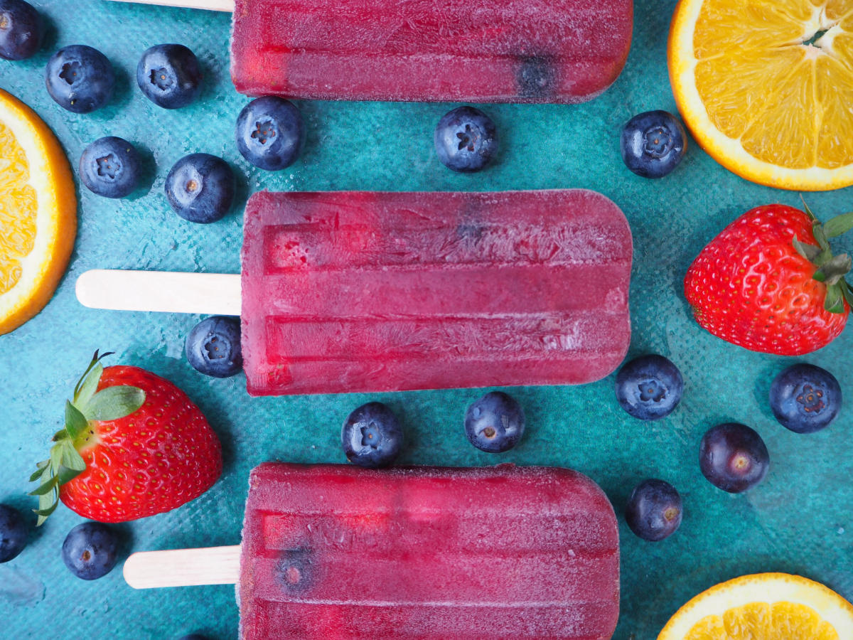 Close up of vertical row of three non alcoholic sangria popsicle, on a green background, surrounded by strawberries, blueberries and orange slices