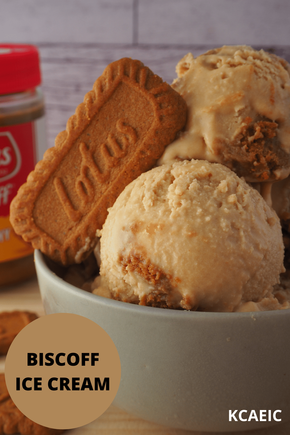 Side view of scoops of biscoff ice cream in grey bowl, with biscuit in ice cream on an an angle, with biscoff jar in the background, and text overlay, biscoff ice cream and KCAEIC.