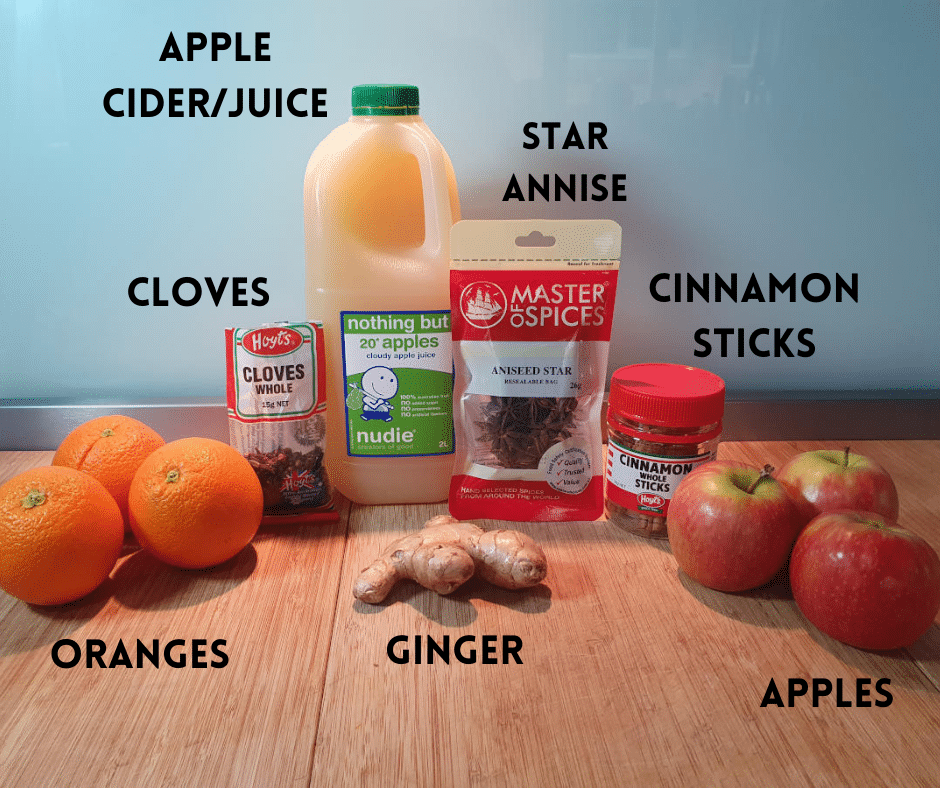 Mulled apple cider ingredients, oranges, whole cloves, ginger root, apple cider or juice, whole star annise, cinnamon sticks and apples.