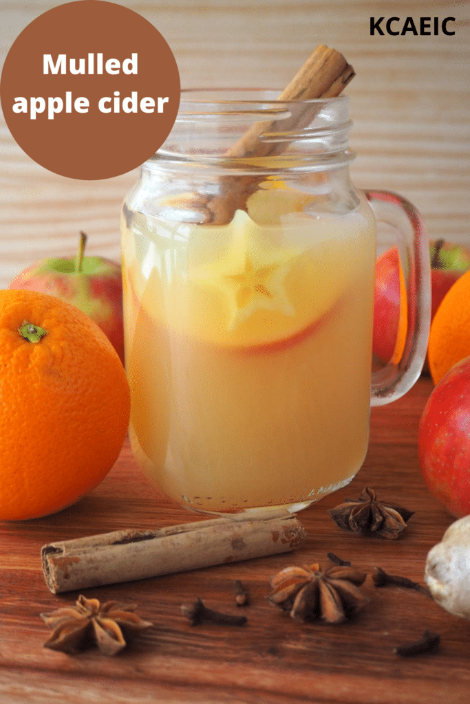 side view of a mason jar mug filled with mulled apple cider, with apples, oranges and spices on the side, on a brown board with a light brown background, with text overlay, mulled apple cider and KCAEIC.