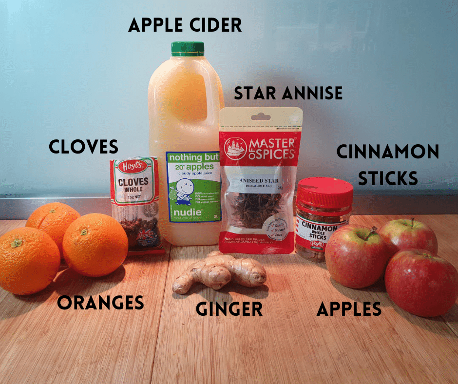 Mulled apple cider popsicle ingredients, oranges, whole cloves, ginger root, apple cider or juice, whole star anise, cinnamon sticks and apples.