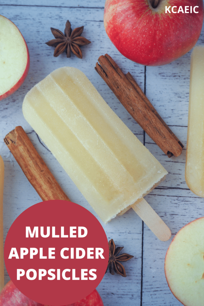 Top down view of mulled apple cider popsicle, with apple, apple star and star anise, with text overlay, mulled apple cider popsicles and KCAEIC.