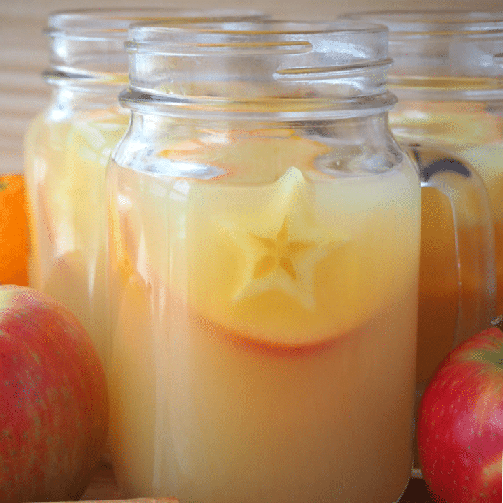 close up side view of a mason jar mug filled with mulled apple cider, with apples and spices on the side, on a brown board with a light brown background.