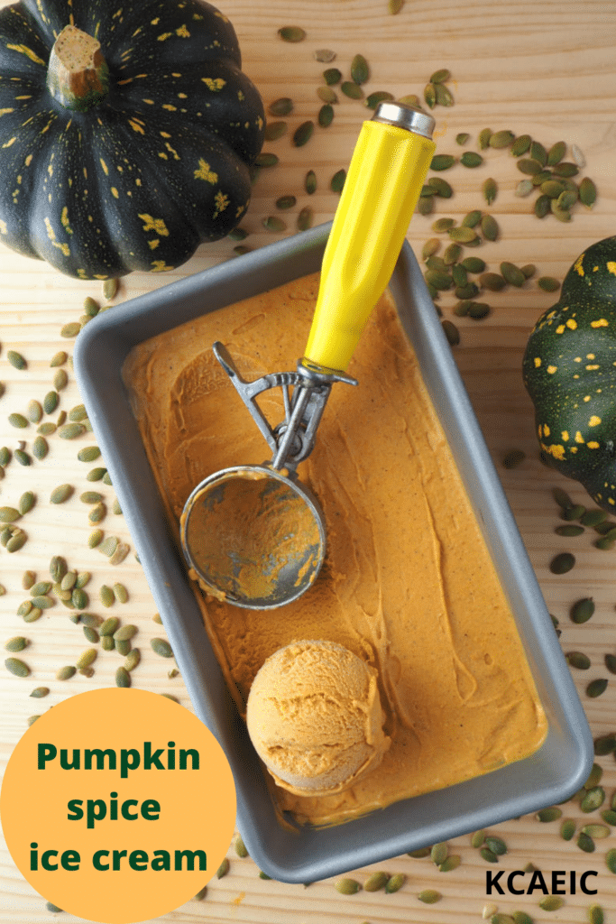 top down view of pumpkin spice ice cream in a loaf pan, with a scooped ice cream and ice cream scoop, on a wooded background with two pumpkins on the side and pumpkin seeds scattered around, and text overlay, pumpkin spice ice cream and KCAEIC.