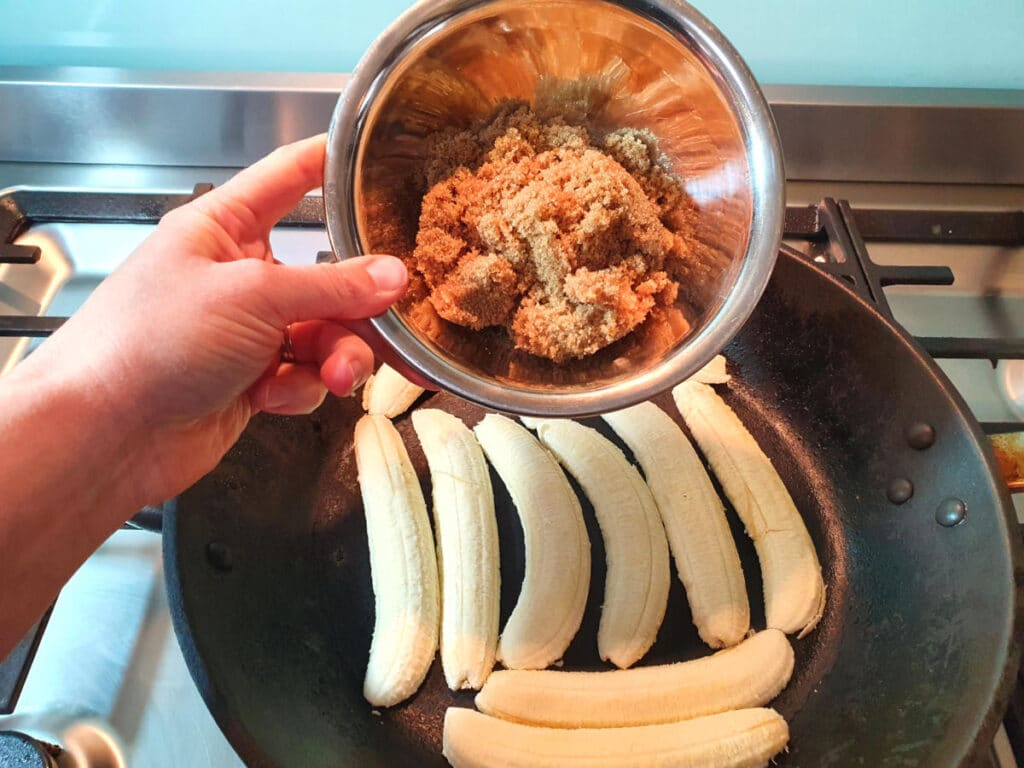 adding brown sugar to slices bananas cooking in a fry pan.