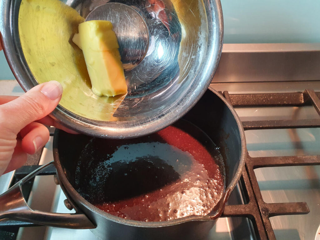 adding butter to pot on stove with chocolate fudge sauce ingredients.
