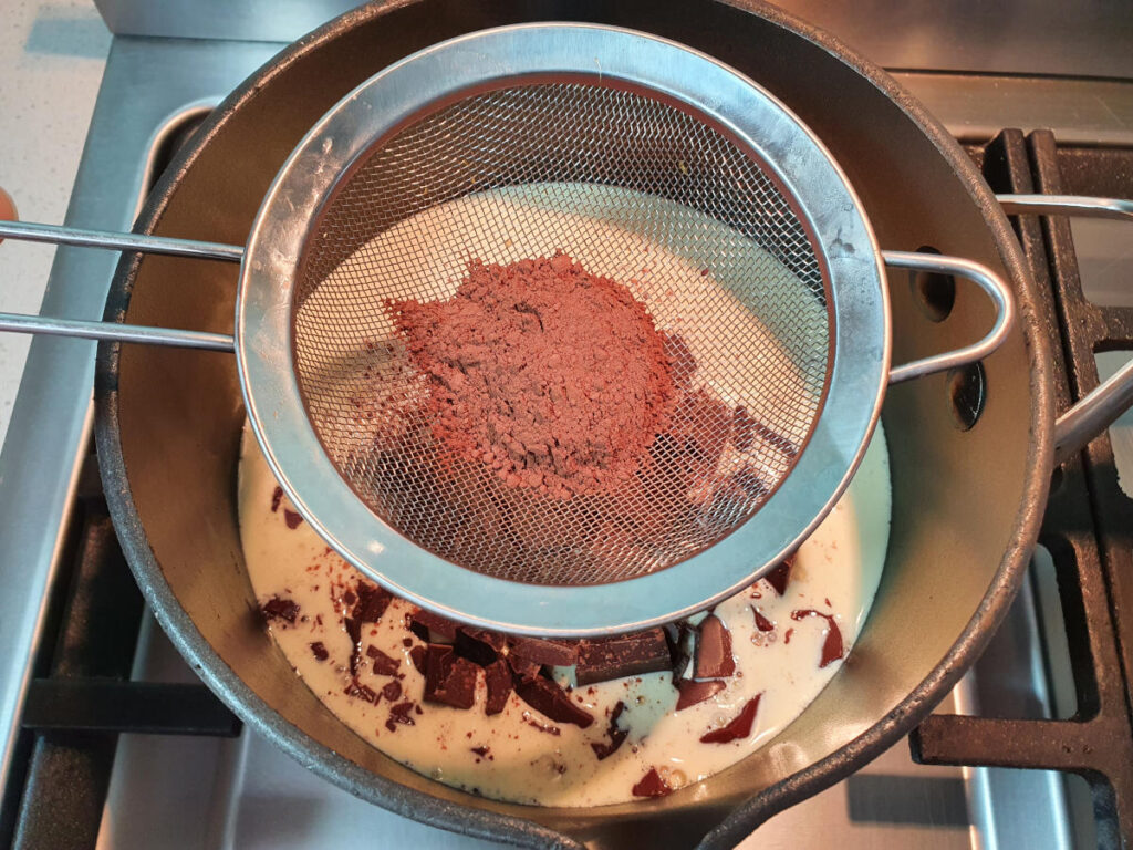 sifting cocoa powder over a pot on the stove with chocolate fudge sauce ingredients.