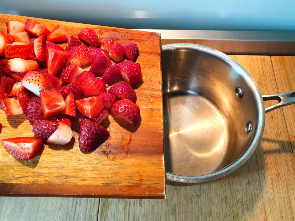 adding chopped strawberries to pot.