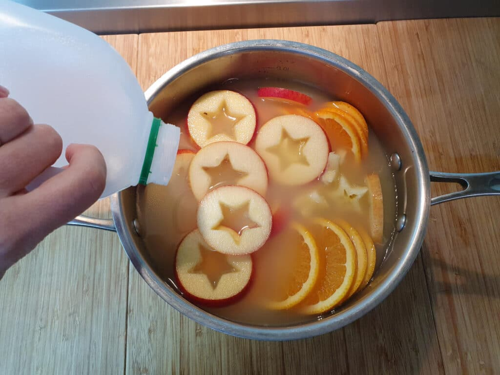 pouring apple cider into pot with sliced apple and oranges.
