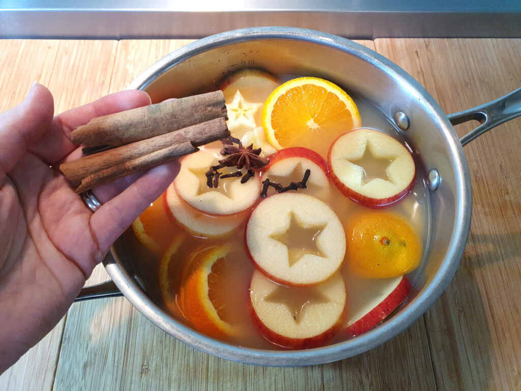 adding cinnamon sticks to pot containing sliced apples, oranges, cloves and star annise on a chopping board.