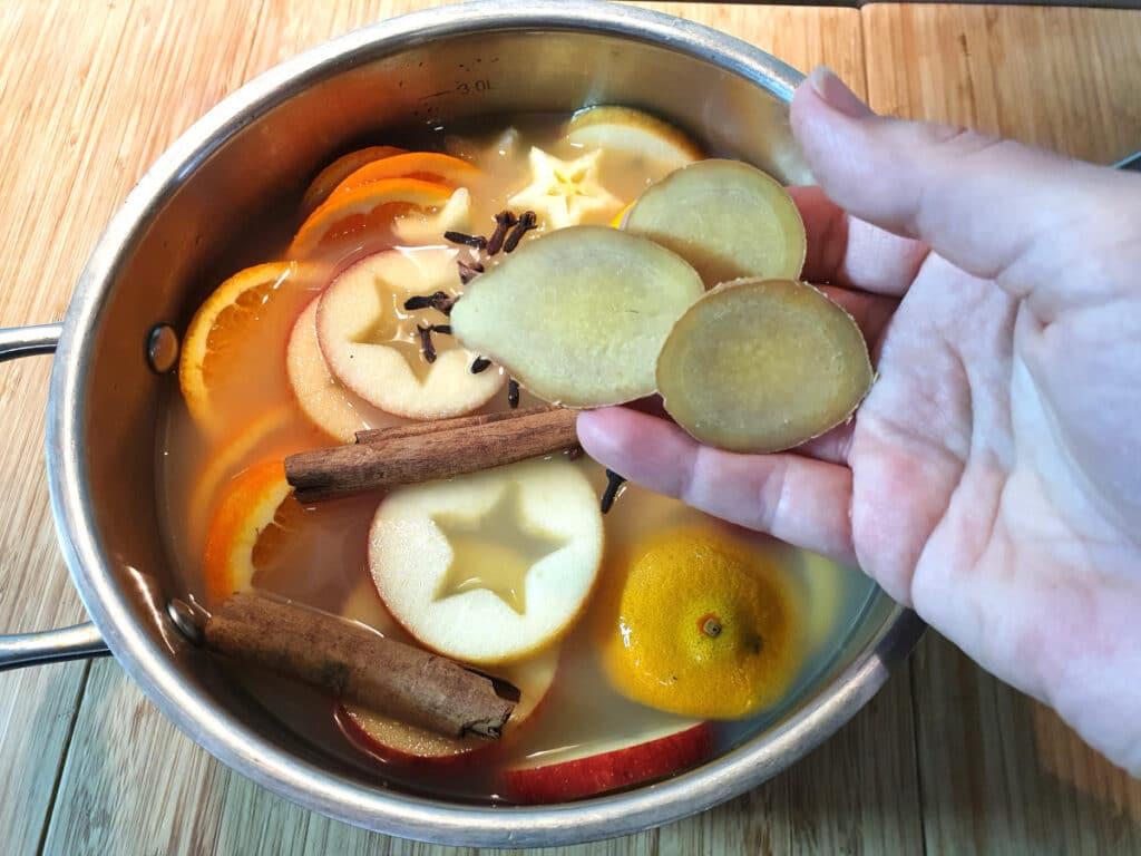 Adding sliced ginger to pot.