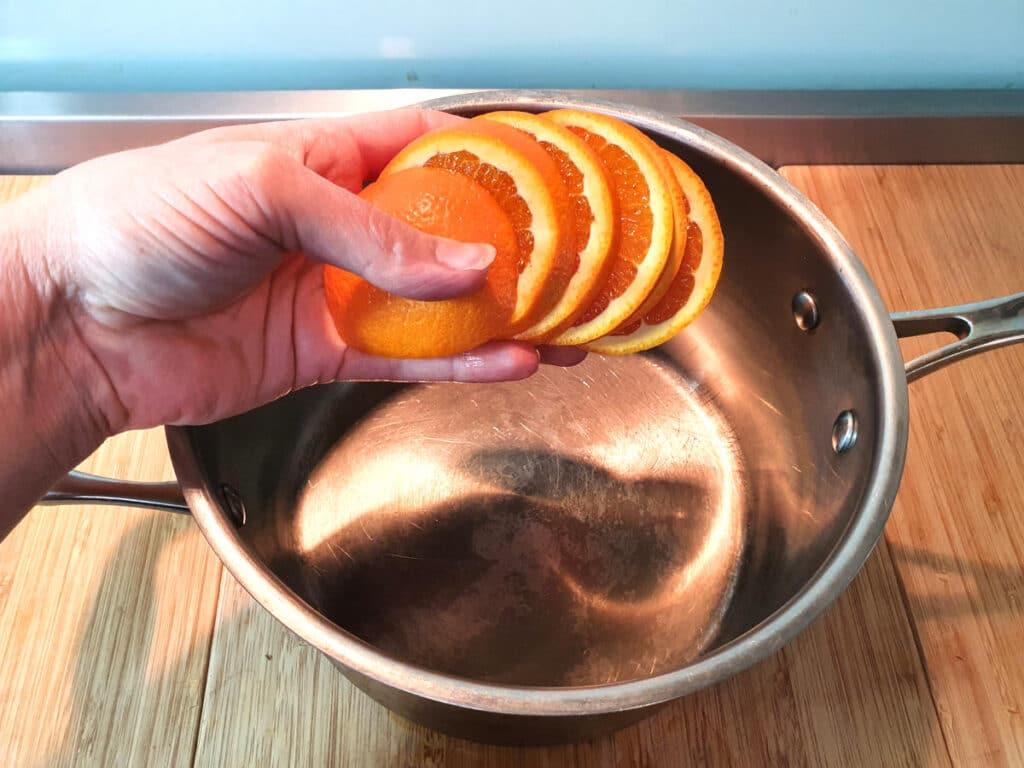 Adding sliced oranges to pot.