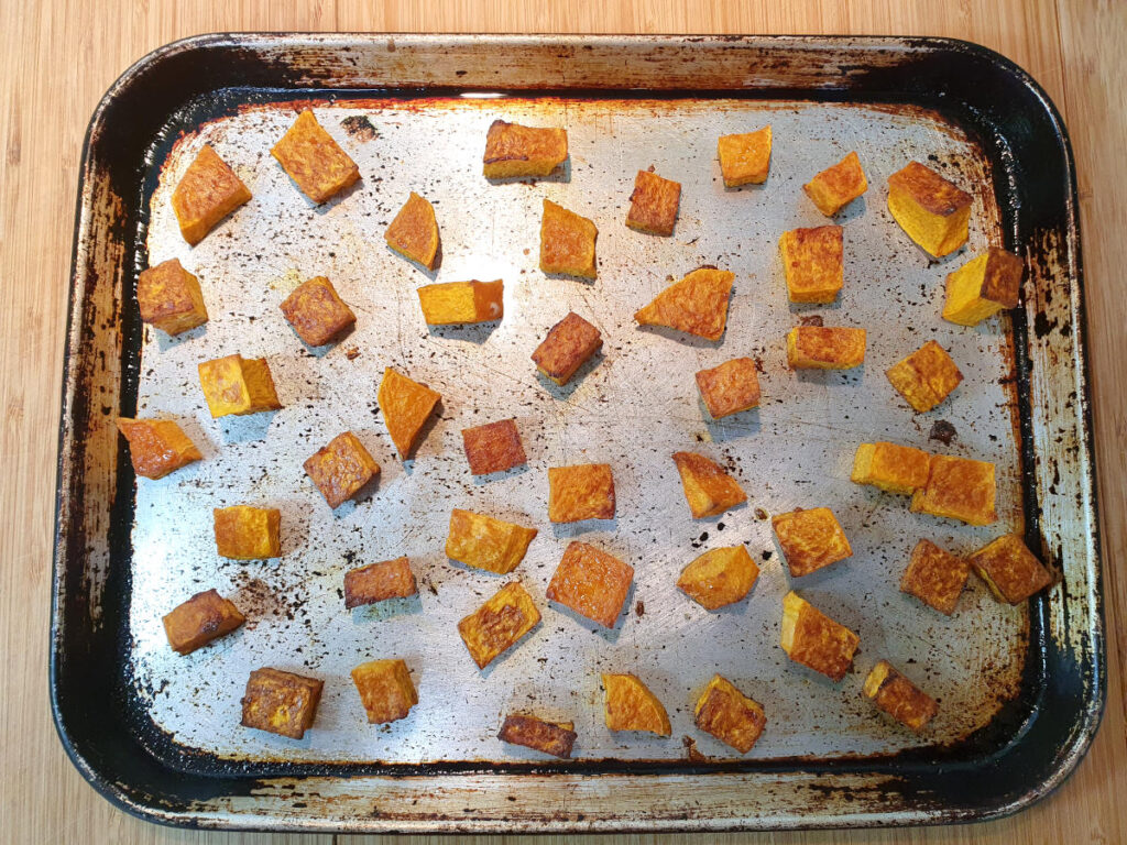 Top down view of roasted pumpkin on a baking tray, on chopping boards.