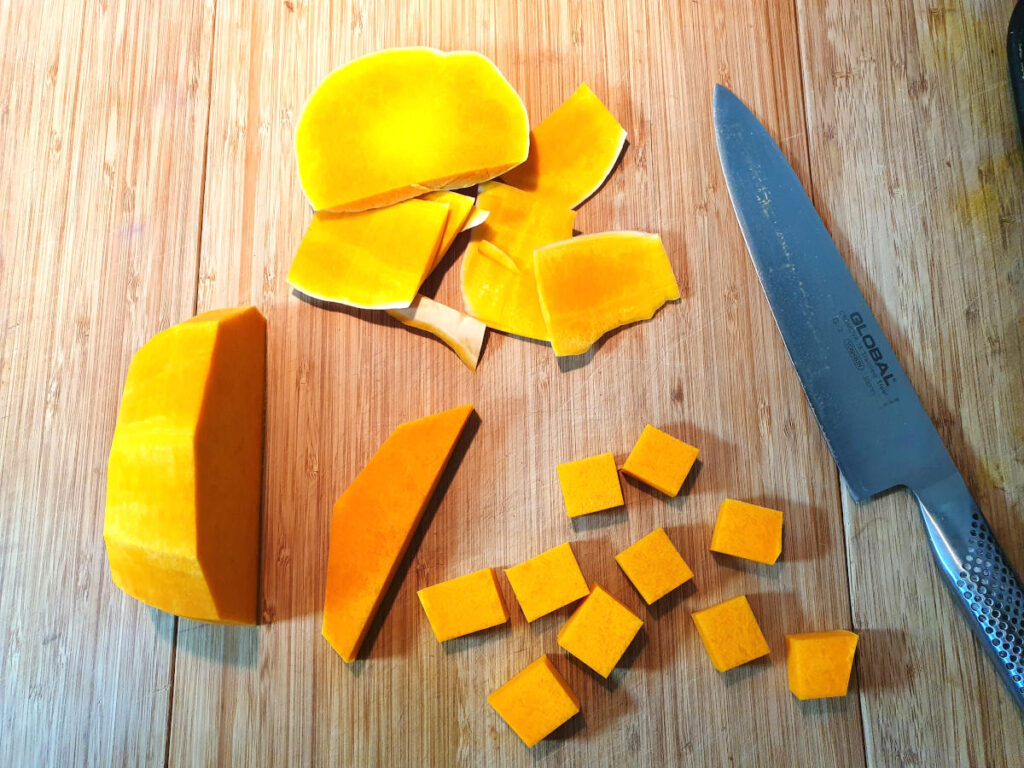 Top down showing pumpkin chopped up at various of chopping, with a large knife, on a chopping board.