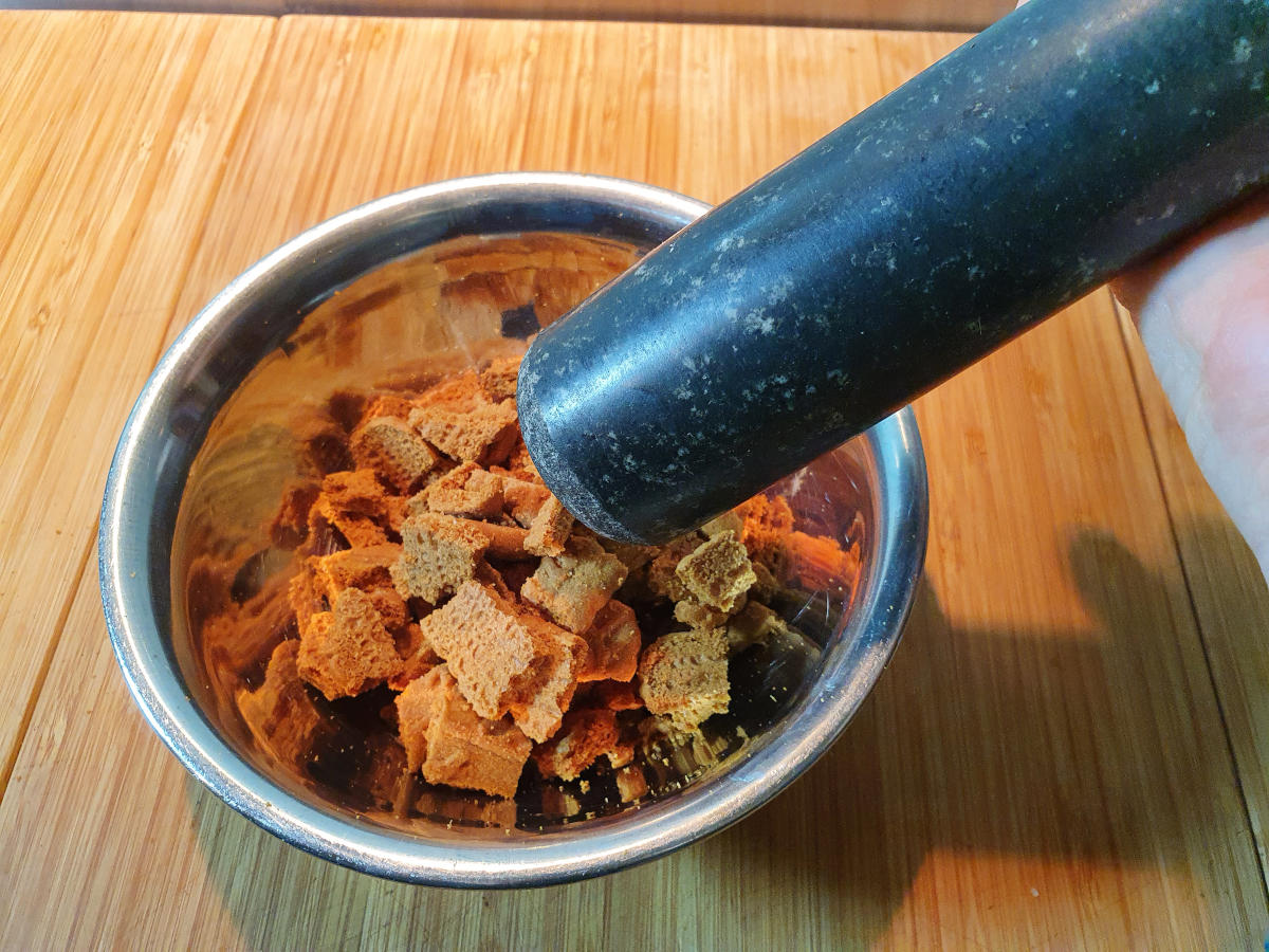 crushing up biscoff biscuits in a metal bowl with a stone pestle, on a wooded chopping board.