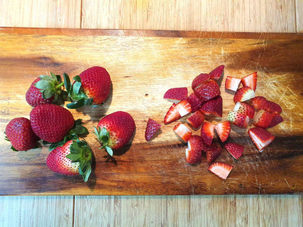 cutting up strawberries on a chopping board.