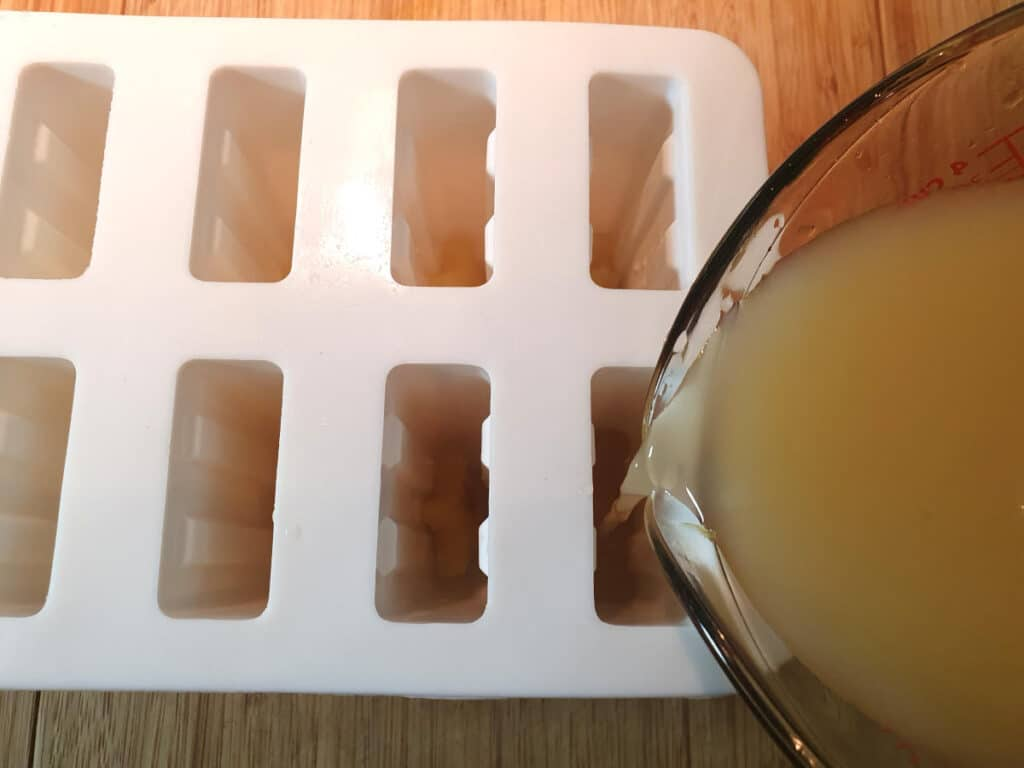 filling popsicle moulds with popsicle mix.