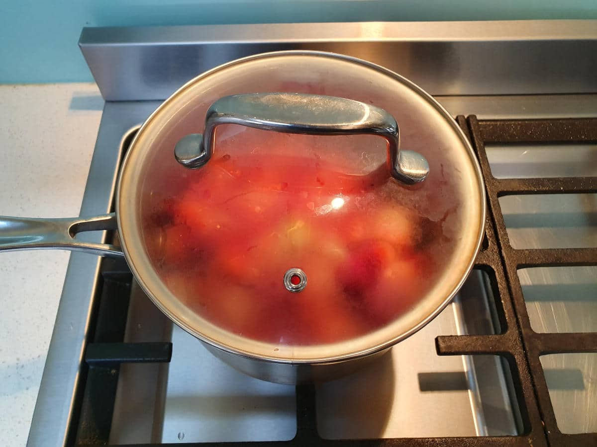 strawberry sauce in pot on stove with lid on.